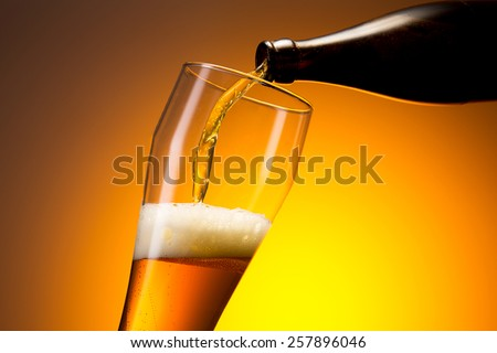 wheat beer pouring out of a bottle - stock photo