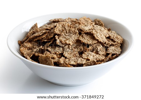 Wheat bran breakfast cereal with no milk in a bowl isolated on white background. - stock photo