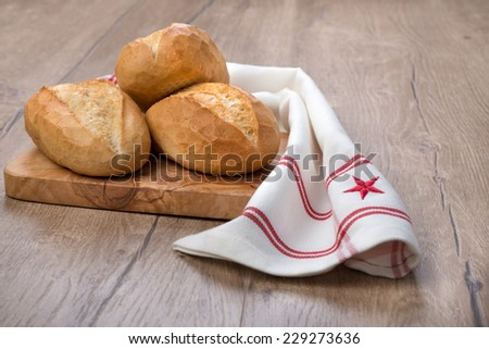Wheat bread rolls on a cutting board with striped towel - stock photo