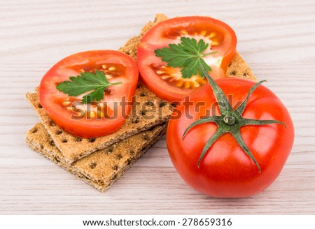 Wheat crisp bread and tomato on wooden table - stock photo