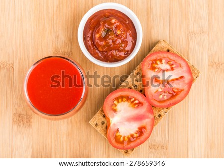 Wheat crisp bread, bowl with ketchup and tomato juice in glass on bamboo board, top view - stock photo