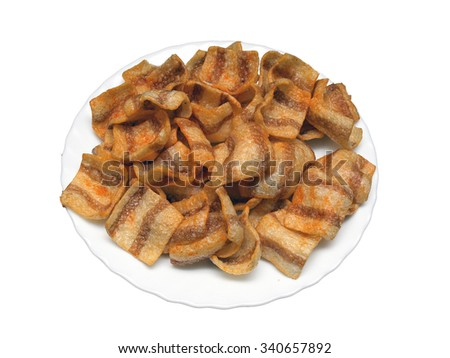 Wheat crisps made as fried beacon slices on white dish close up isolated with clipping path on white background. - stock photo