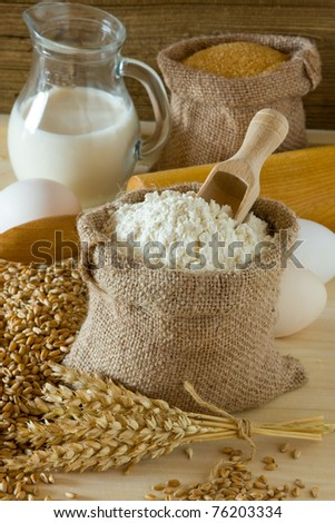 Wheat ears and flour in burlap sack - stock photo