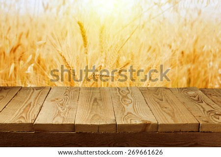 Wheat field background and empty wooden deck table  - stock photo