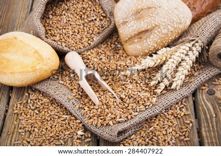 wheat grain in a small bag and different bread on a wooden background - stock photo