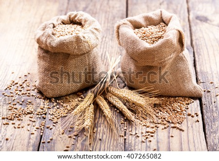 wheat grains in sacks on wooden table - stock photo