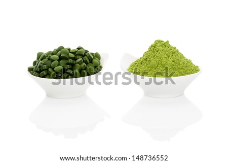 Wheat grass powder and green chlorella pills in two bowls isolated on white background. Alternative herbal medicine. - stock photo