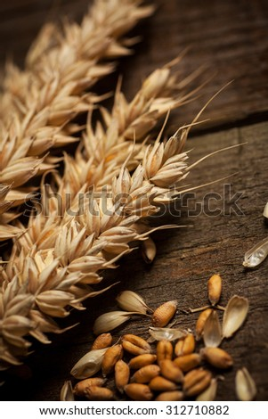Wheat sheaves on a textured wooden background.