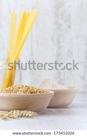 Wheat, Spaghetti and Flour on wooden table - stock photo
