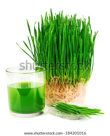 Wheatgrass juice with sprouted wheat on the plate isolated on white background - stock photo