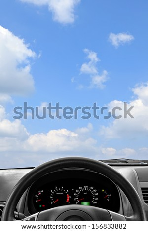 Wheel and dashboard of a car on the cloudy sky background - stock photo