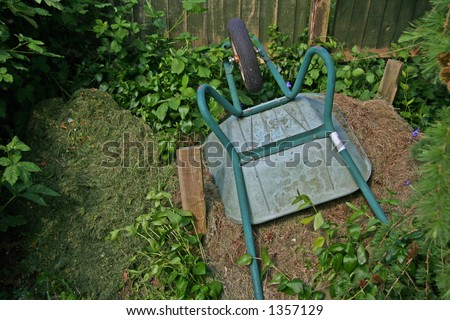 Wheel Barrow lying on a compost heap - stock photo