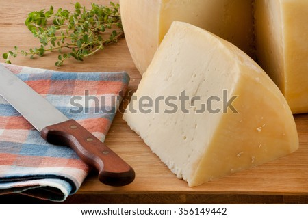 Wheel cheece on wooden plato decorated with oregano and table cloth. - stock photo