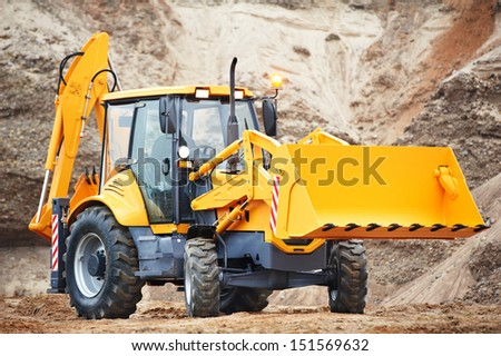 Wheel excavator loader with risen bucket at eathmoving works in construction site or sandpit - stock photo