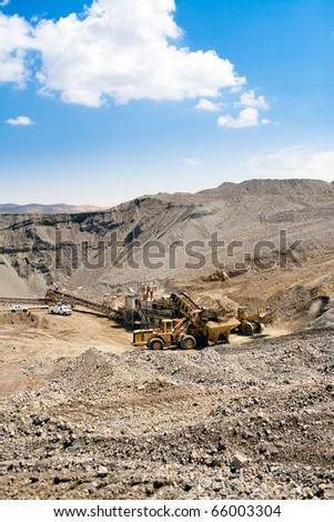 Wheel front-end loader unloading ore into bunker  which is transported by conveyor belt to to Processing Plant - stock photo