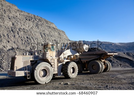 Wheel front-end loader unloading ore into heavy dump truck at the opencast mining - stock photo