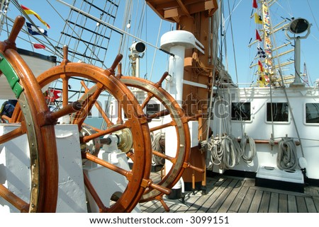 Wheel helm an deck of a large sail boat - stock photo
