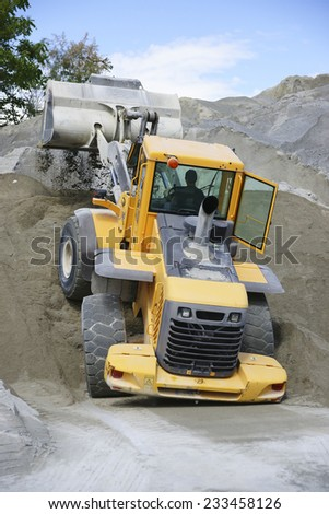 Wheel loader Excavator unloading sand during earth moving works at quarry. - stock photo
