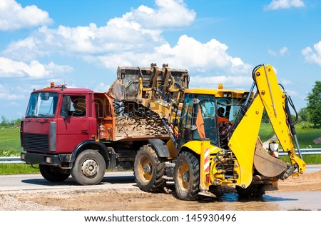 Wheel loader Excavator unloading sand into truck body during earthmoving works at construction site - stock photo