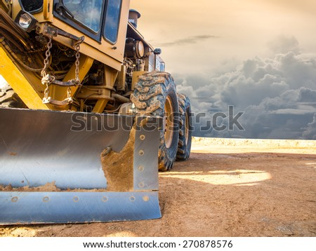 Wheel loader Excavator with backhoe unloading sand at eath works in construction site - stock photo
