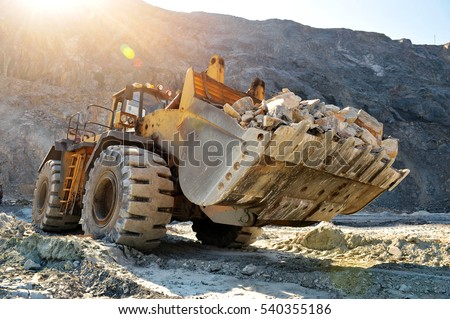 Wheel loader machine unloading rocks in the open-mine of iron ore