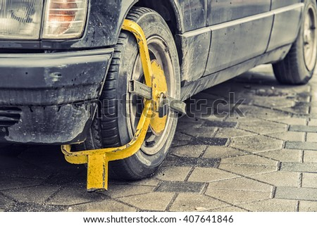 Wheel lock on an illegally parked car - stock photo