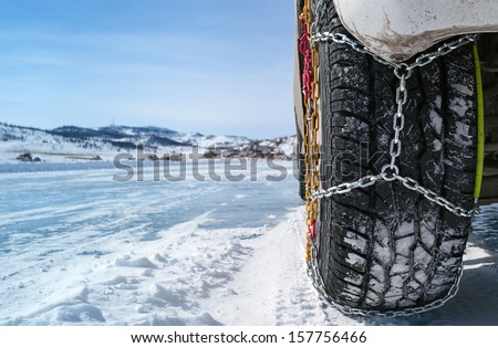 wheel of a car with chains on snow - stock photo