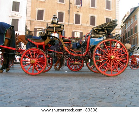 wheel of a horse carriage in Rome Italy with other red wheels in the background