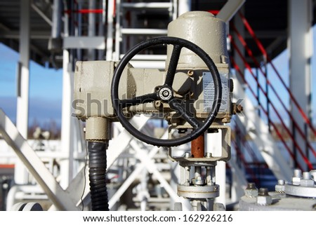 wheel of a large valve at a chemical plant after rain - stock photo