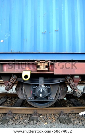 Wheel of a train loaded with a cargo container - stock photo