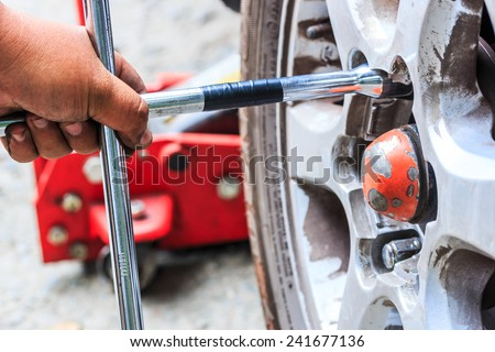 Wheel, technician changing wheel on car with a wrench - stock photo