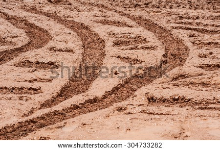 Wheel track on ground muddy mess.