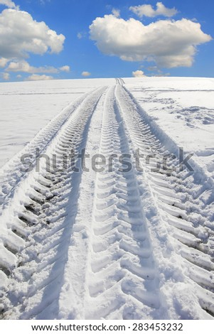 wheel tracks from a truck tire in winter landscape - stock photo