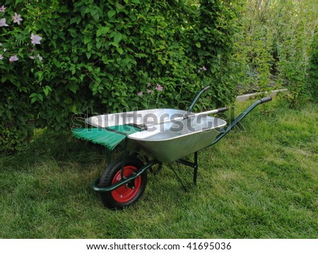 Wheelbarrow and broom on green grass in garden - stock photo