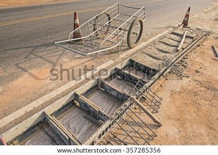wheelbarrow and traffic cone on road - construction site. Concrete pavement - sidewalk upgrade - stock photo