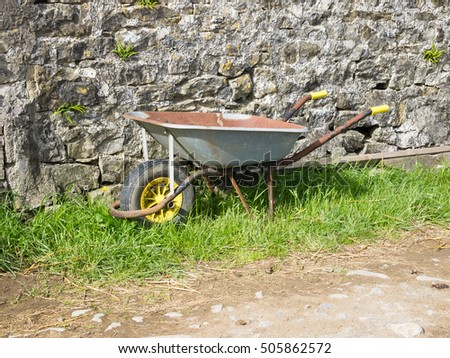 wheelbarrow by rural stone wall