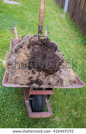 wheelbarrow full of manure and pitchfork on a meadow - stock photo