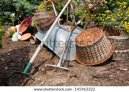Wheelbarrow, grass mower, garden equipment, tools, preparing for planting new plants in the garden - stock photo