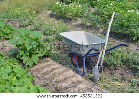 Wheelbarrow with one wheel. It should be among the beds with crops. Shovel and pitchfork leaning against the wheelbarrow. Close-up / wheelbarrow, shovel, pitchfork / Feodor Eremin
