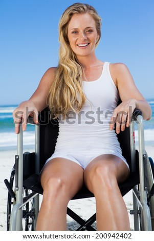 Wheelchair bound blonde sitting on the beach smiling at camera on a sunny day - stock photo