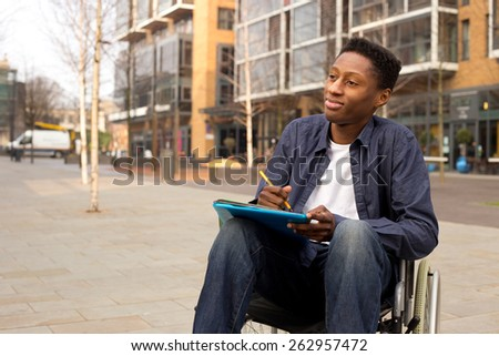 wheelchair bound man looking thoughtful with folders and a pen - stock photo