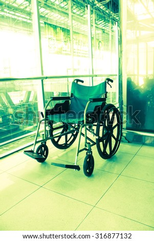 Wheelchair service in airport terminal, vintage color style - stock photo
