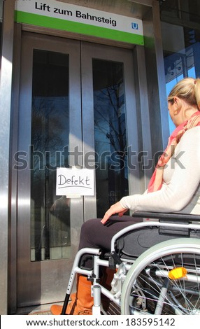 Wheelchair user on a defect elevator - stock photo