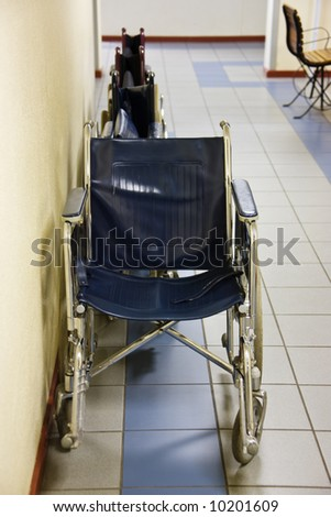 Wheelchairs parked on the side of a hospital hallway. - stock photo