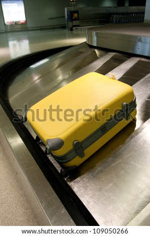 Wheeled suitcase on baggage carousel in airport - stock photo