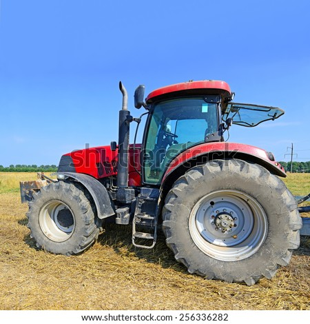 Wheeled tractor in the field - stock photo