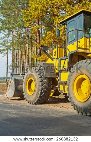 wheelloader in forest near edge of road rear view   - stock photo