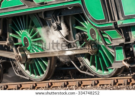 wheels and coupling rods on a vintage steam locomotive - shallow d.o.f. - stock photo