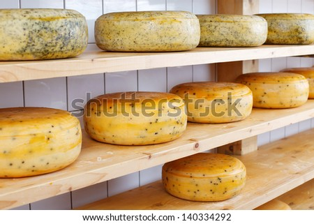 Wheels of cheese seasoned with herbs maturing on shelves in a storage unit - stock photo