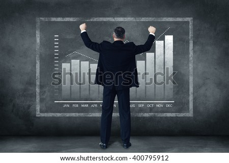 When business goes well. Rear view full length of mature businessman holding arms outstretched while standing against grey background with illustration of chart - stock photo